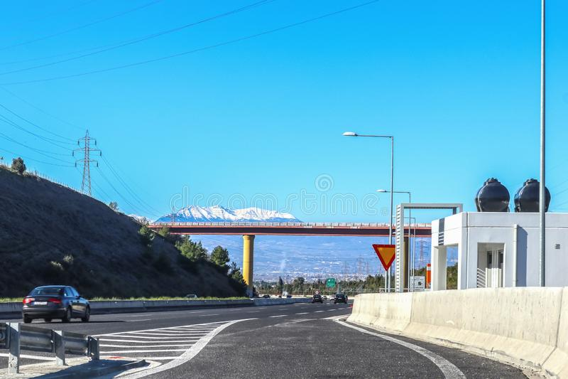 雅典的路旁卫生间有伯罗奔尼撒积雪的山距离的和云彩的科林斯湾高速公路的希腊  库存图片
