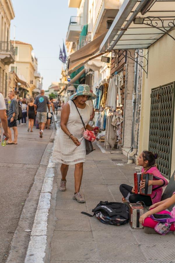 雅典,希腊- 2018年9月16日:播放在雅典街道的年轻可怜的女孩一部手风琴 库存照片