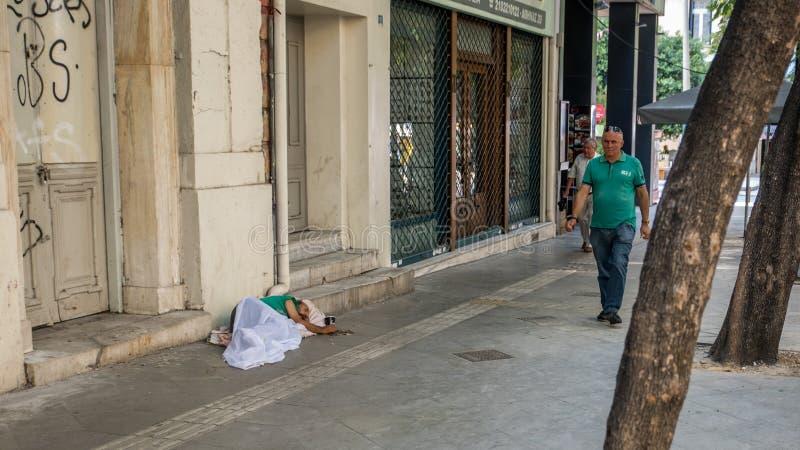 雅典,希腊8月17日2018年:睡觉在边路的无家可归的人 免版税库存图片