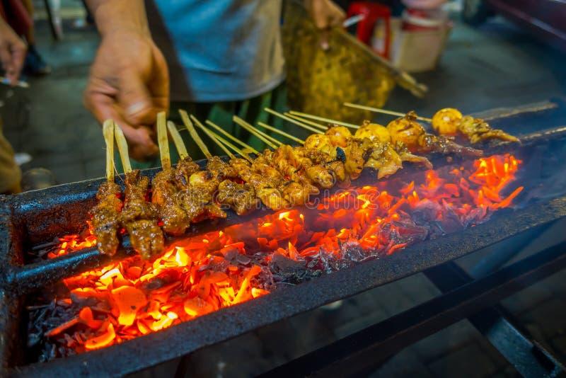 雅加达,印度尼西亚:街道烤肉用肉串起烧得发嘶声,非常热的火准备食物的燃烧和人 免版税库存照片
