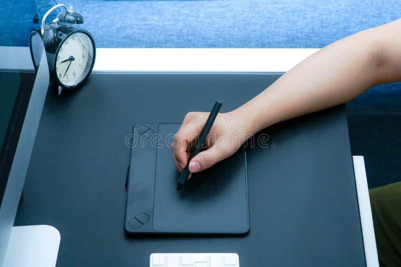 集中于研究计算机的繁忙的图表设计师在数字式笔老鼠旁边 免版税图库摄影