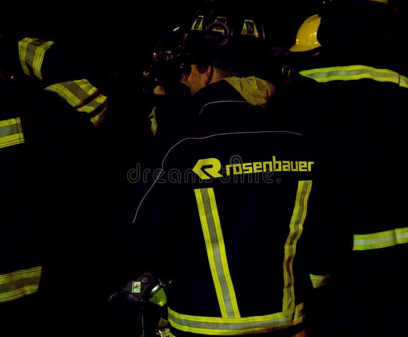 集中于Rosenbauer地堡齿轮的南非消防队员在晚上 免版税图库摄影