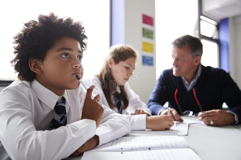 集中佩带一致的工作的男性高中生在与老师的表上谈话与学生在背景中 库存照片