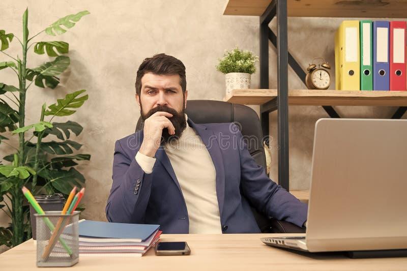 集中和焦点 人有胡子的上司坐有膝上型计算机的办公室 解决业务问题的经理 ?? 免版税库存照片