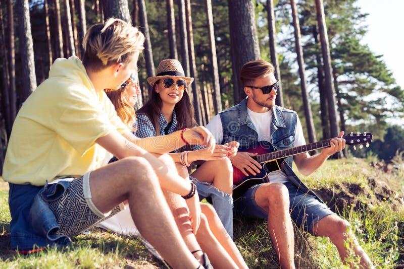 集会和听到音乐的小组朋友在日落 图库摄影