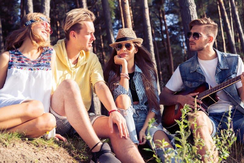 集会和听到音乐的小组朋友在日落 免版税图库摄影