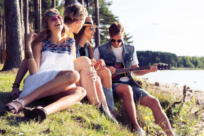 集会和听到音乐的小组朋友在日落 库存照片