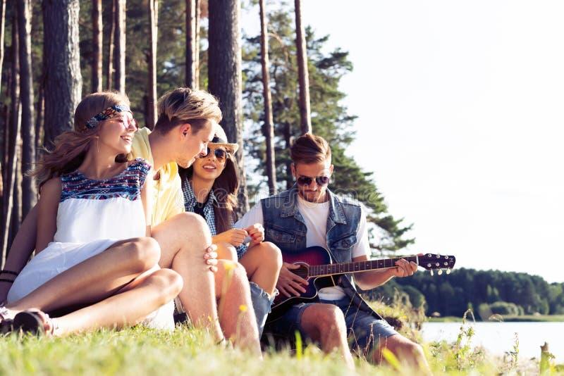 集会和听到音乐的小组朋友在日落 免版税库存图片