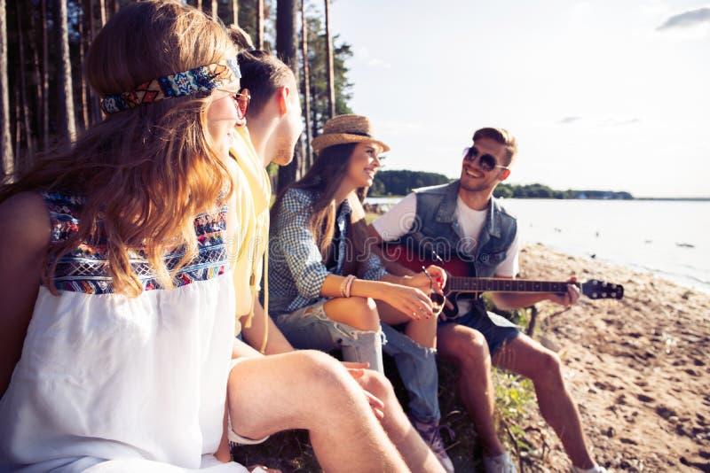 集会和听到音乐的小组朋友在日落 免版税库存照片