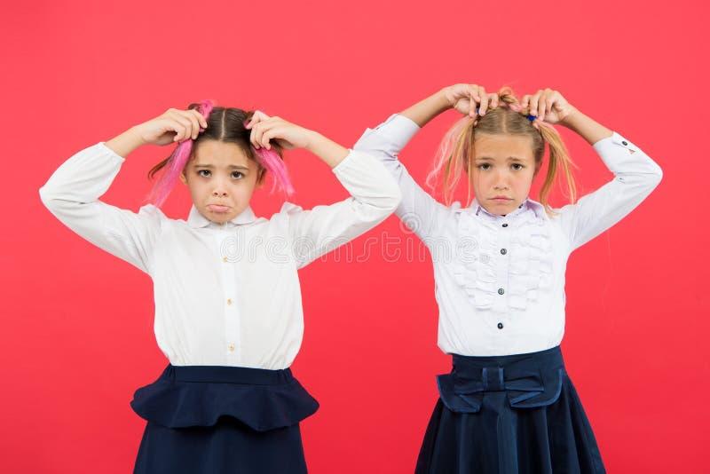 集会新的朋友在学校 学校友谊 应该教育是更多乐趣 有逗人喜爱的发型和哀伤的面孔的女小学生 免版税库存图片