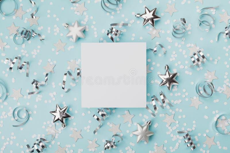 集会狂欢节圣诞节大模型装饰的confett和银色星在绿松石背景顶视图 平的位置 假日邀请 免版税库存图片