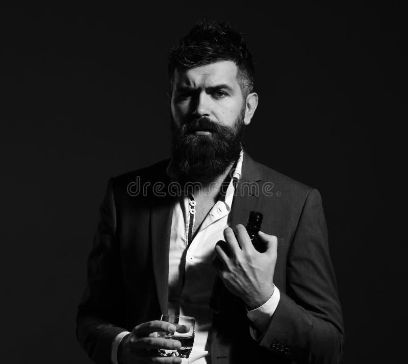 集会的和饮用的概念 有胡子品尝酒精的斟酒服务员 与严肃的面孔的商人 免版税库存图片