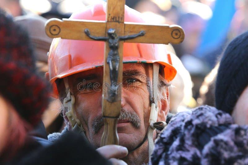 集会的矿工拿着在他的面孔前面的一幅耶稣受难象 免版税库存照片
