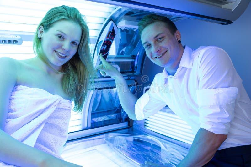 雇员在日光浴室建议顾客或客户在晒黑的床 库存图片