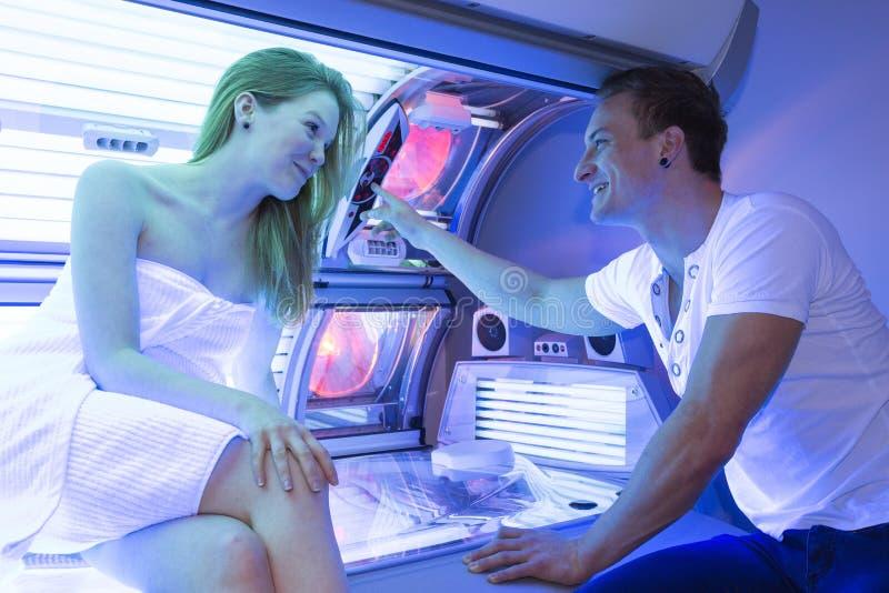 雇员在日光浴室建议顾客或客户在晒黑的床 库存照片