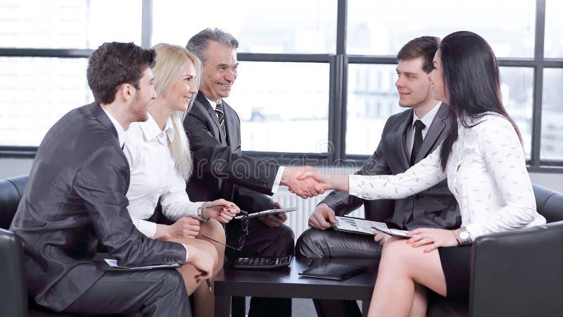 雇员看商务伙伴握手  免版税图库摄影