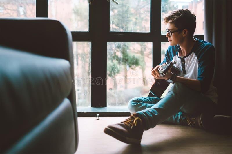 雍人在吉他使用坐地板在客厅 图库摄影