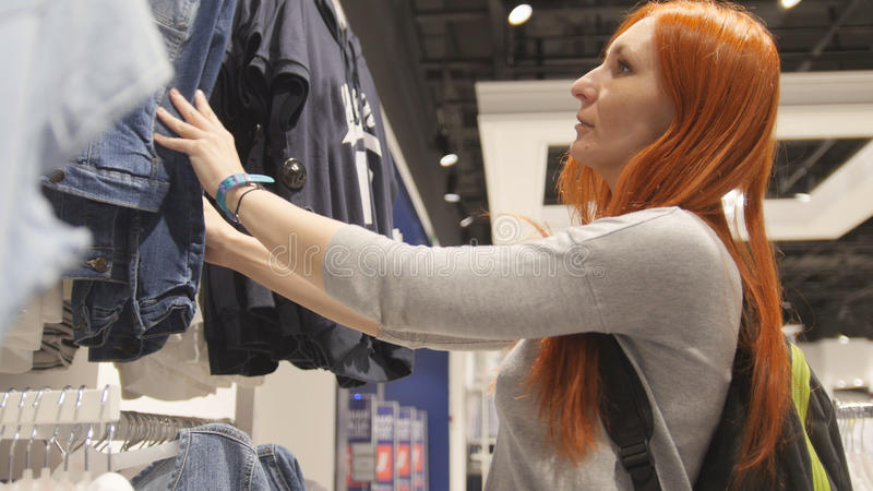 雍正面妇女选择在妇女` s服装店的一件礼服 免版税库存图片