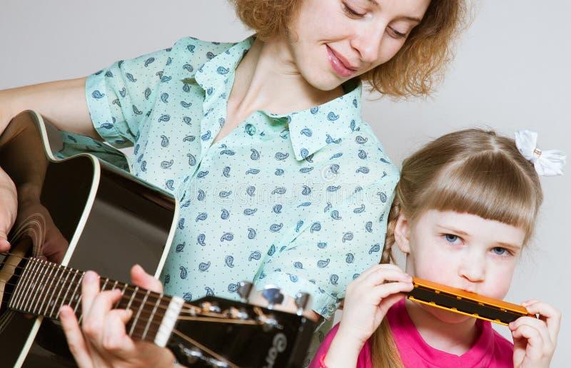 雍母亲nd她使用在音乐instru的俏丽的女儿 库存图片