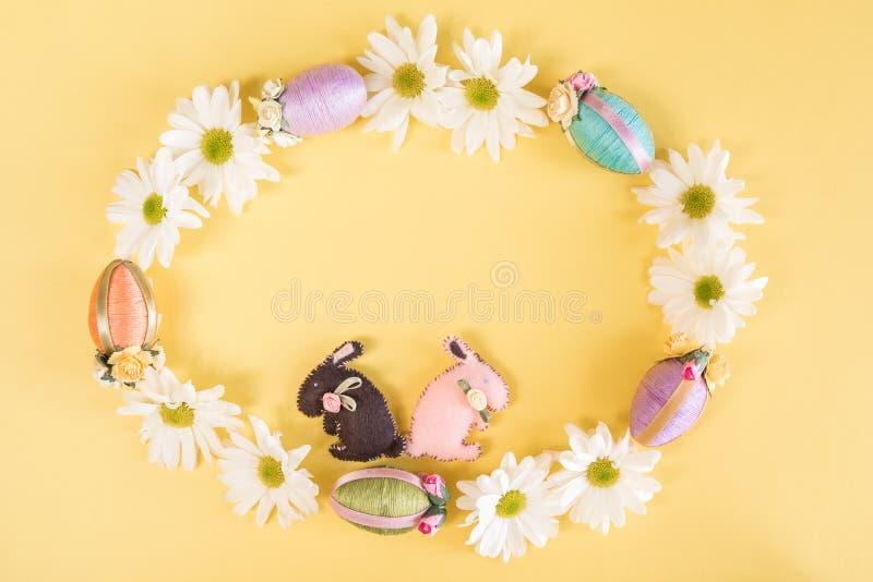 雏菊、复活节彩蛋和复活节兔子花圈在坚实淡色黄色背景 库存图片