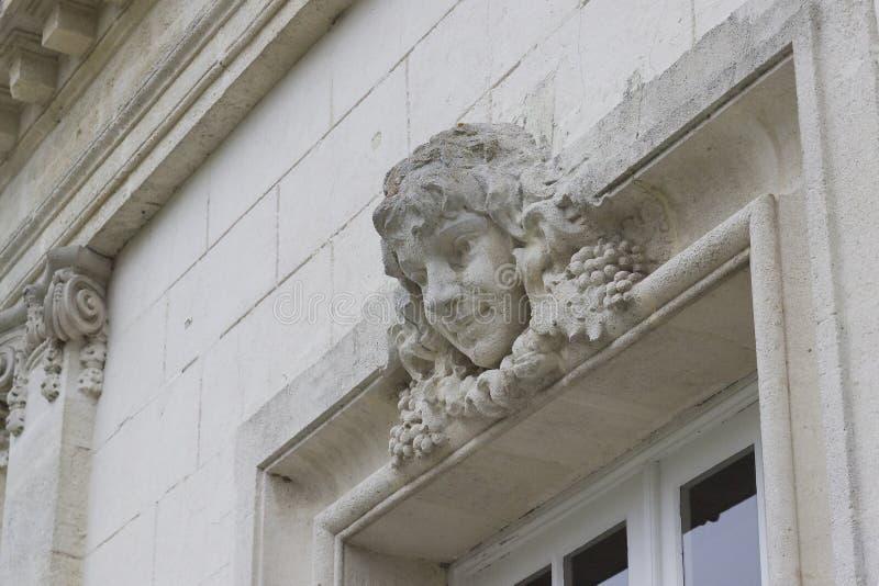 雕刻一个女孩的头在窗口上的在法国城堡 图库摄影