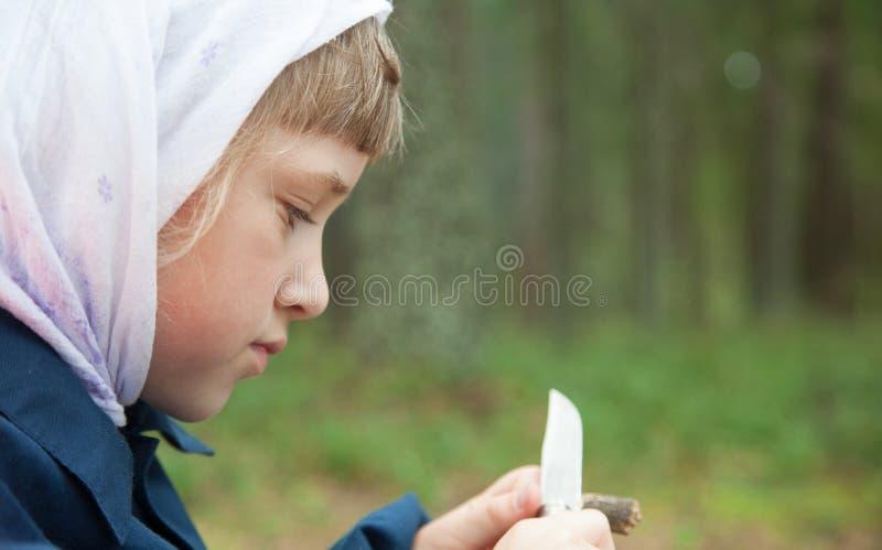 雕刻一个木玩具的逗人喜爱的女孩 库存照片