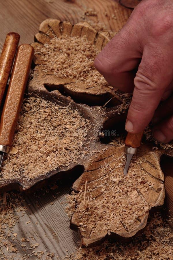 雕刻与凿子的人木头 图库摄影