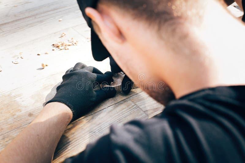 雕刻从木头的手匙子,与凿子关闭一起使用 做木匙子、凿子和削片的过程在肮脏的桌 免版税库存照片