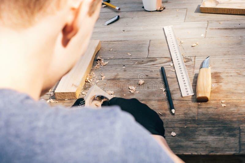 雕刻从木头的手匙子,与凿子关闭一起使用 木车间 做木匙子的过程,凿子,铅笔, 库存图片