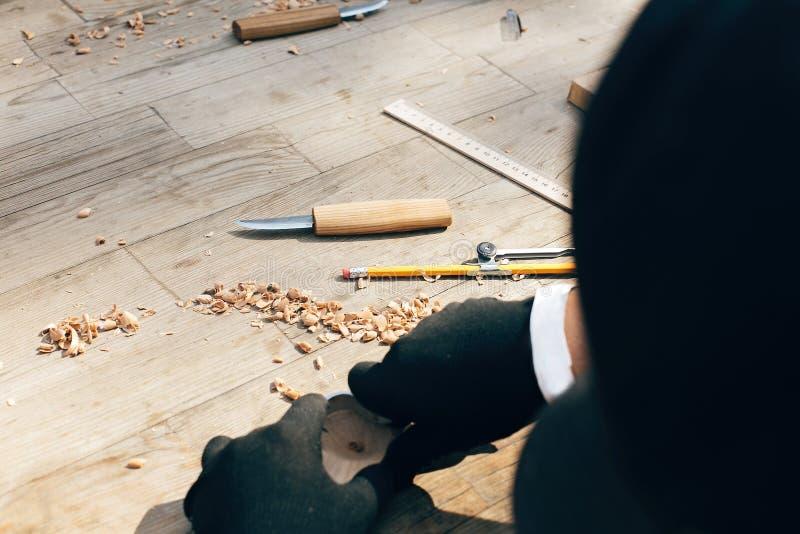 雕刻从木头的手匙子,与凿子关闭一起使用 木车间 做木匙子的过程,凿子,铅笔, 图库摄影