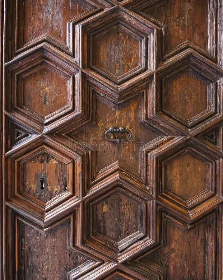 雕刻几何样式装饰装饰品的古老华丽木门 免版税库存照片