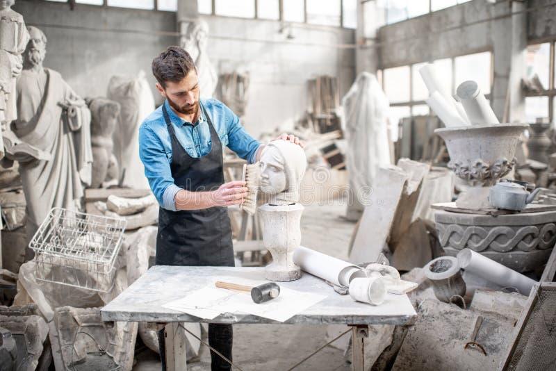 雕刻家与雕塑一起使用在演播室 库存图片