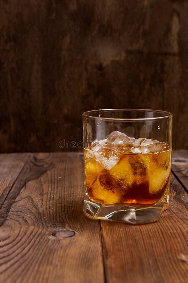 雕琢平面的杯与冰的威士忌酒 免版税库存照片