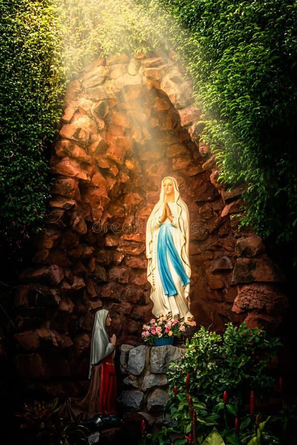 雕象圣母玛丽亚立场祈祷 库存图片