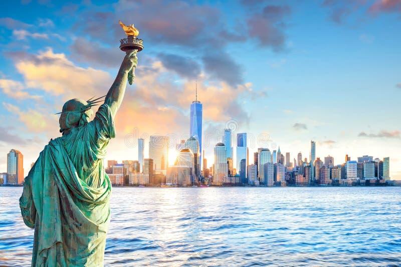 雕象在日落的自由和纽约地平线 库存图片