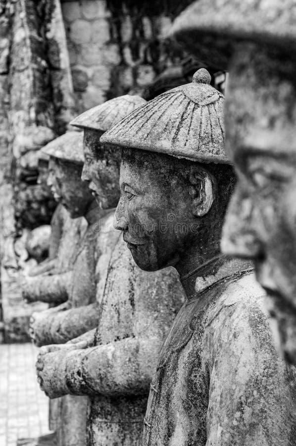 雕象行的面孔在阮福昶皇帝的陵墓的颜色的,越南,有其他雕象的在背景中 免版税图库摄影