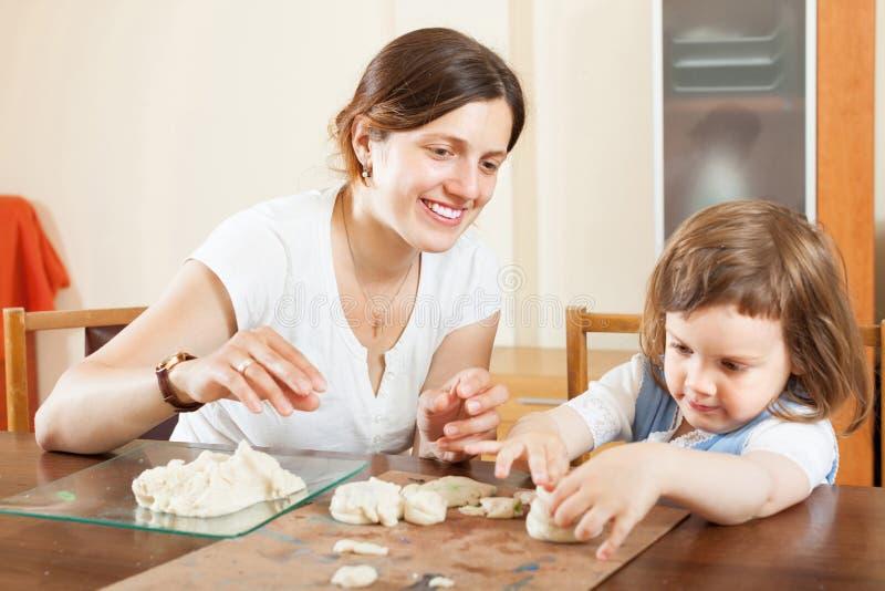 雕刻从黏土或面团的少妇和她的孩子在家 免版税库存照片