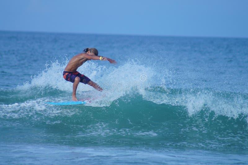 雕刻波浪的冲浪者男孩在NC中外面银行  免版税库存图片