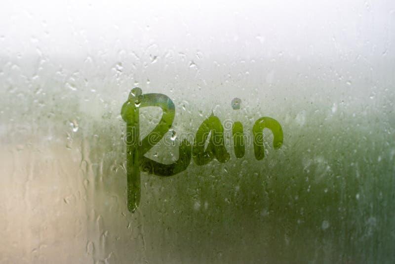 雨在湿气misted的玻璃被写,在玻璃的另一边 库存照片