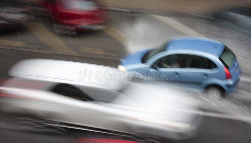 雨天在城市:驾驶在街道的汽车由hea击中了 库存图片