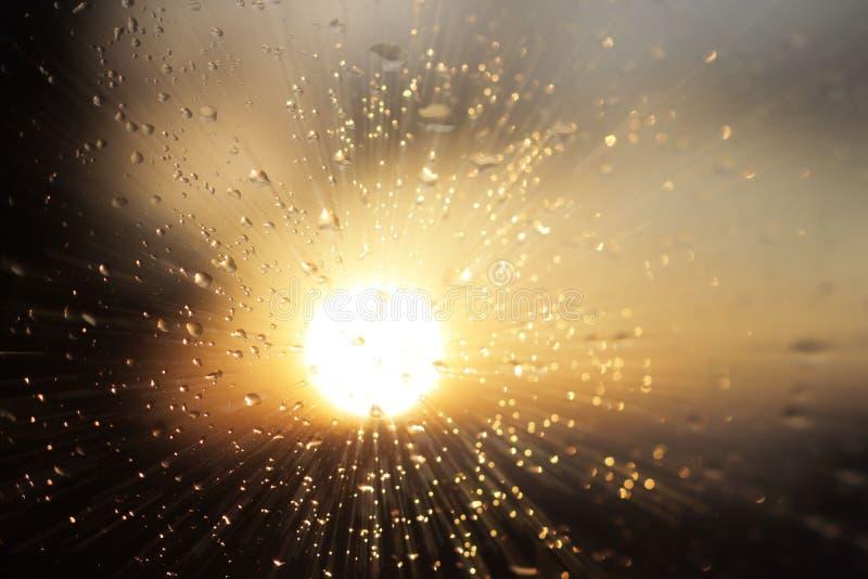 雨宏观摄影在落日的模糊的背景的玻璃下降 在黑暗和橙色口气的纹理 迷离机智 库存照片
