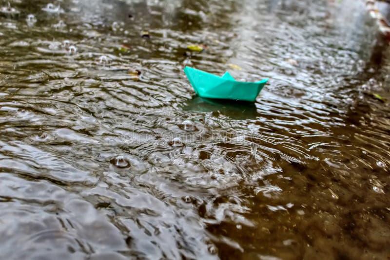 雨水小河运载一艘Origami船 冬天雨在以色列,洪水 库存照片