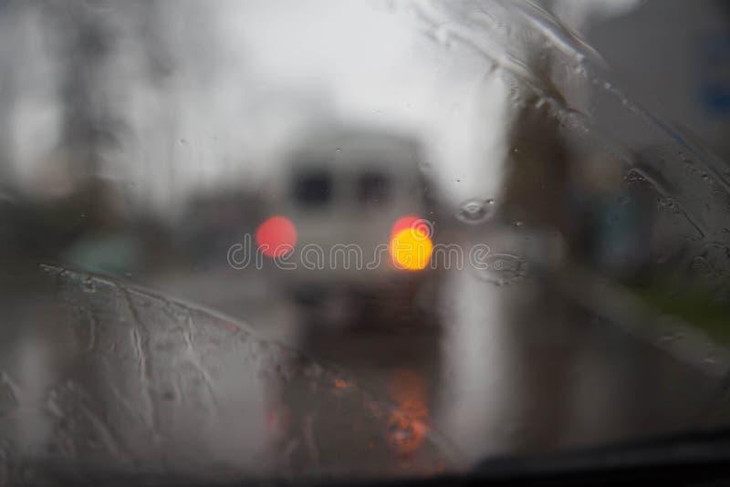 雨水滴在蓝色玻璃背景的 街道在焦点外面的Bokeh光 秋天抽象背景 免版税图库摄影