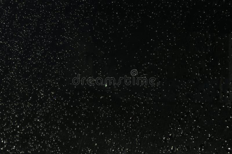 雨水滴的纹理在玻璃的在黑暗 流动在玻璃的水下落下 降雨量夜 免版税库存图片