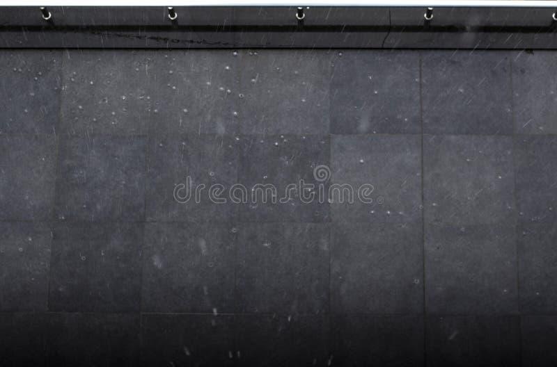 雨珠顶视图落黑地面表面上 免版税库存照片