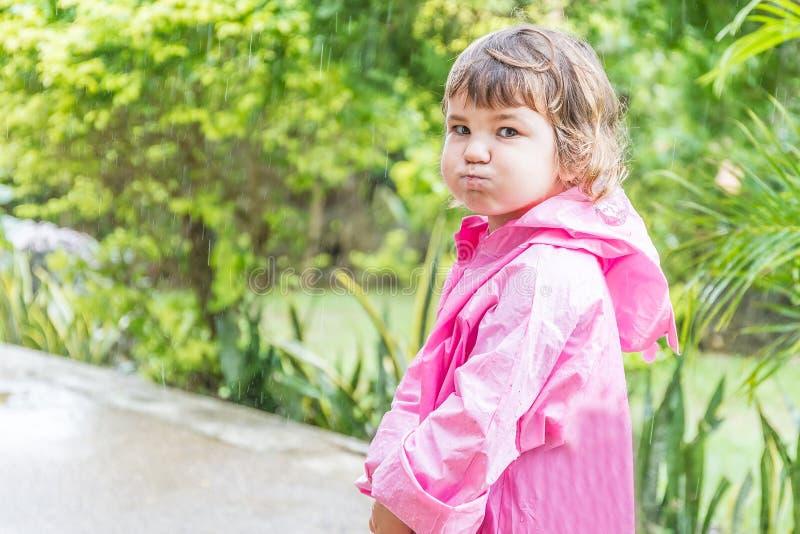 雨衣的儿童女孩在雨下滴下,室外画象 免版税库存图片