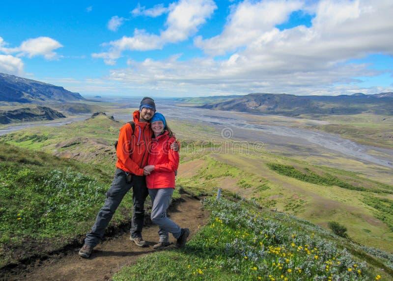 雨衣的愉快的夫妇冒险旅客男人和妇女有瀑布的在背景、自由和活跃生活方式概念中 库存图片