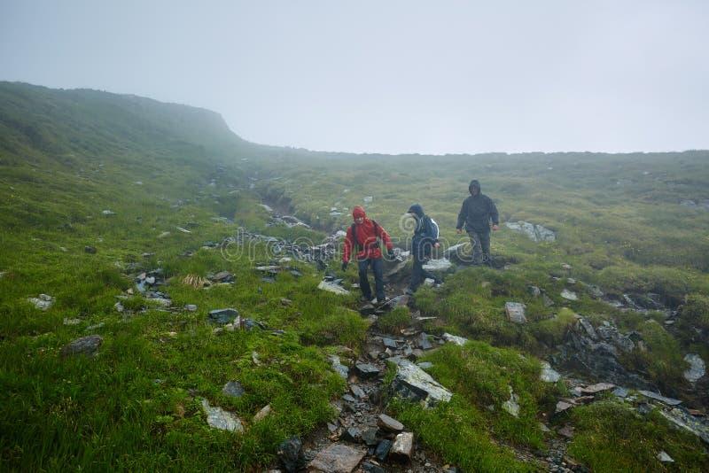 雨衣的远足者在山 免版税库存图片