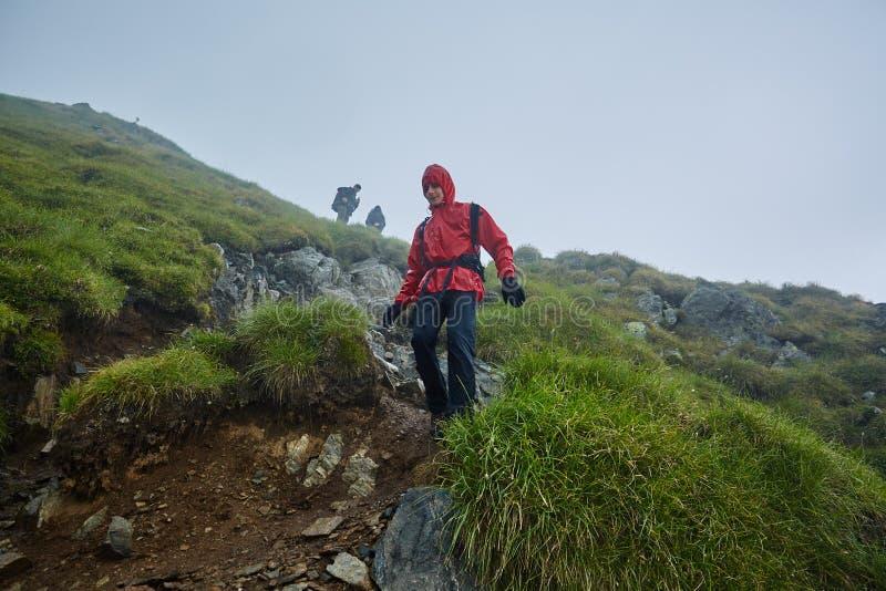 雨衣的远足者在山 库存照片