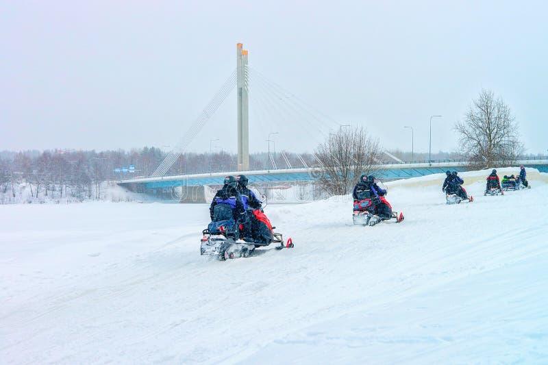 雪上电车的人们在冬天圣诞节的芬兰拉普兰 免版税库存图片